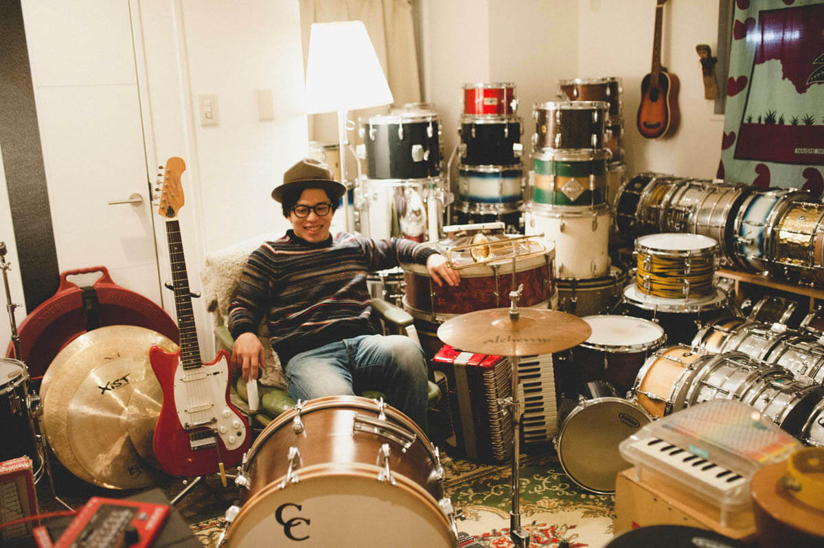 guy sitting down with a collection of best drum kits